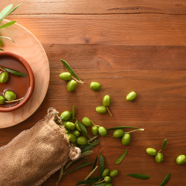 """Sack of harvest raw olives on wooden table top"" stock image"