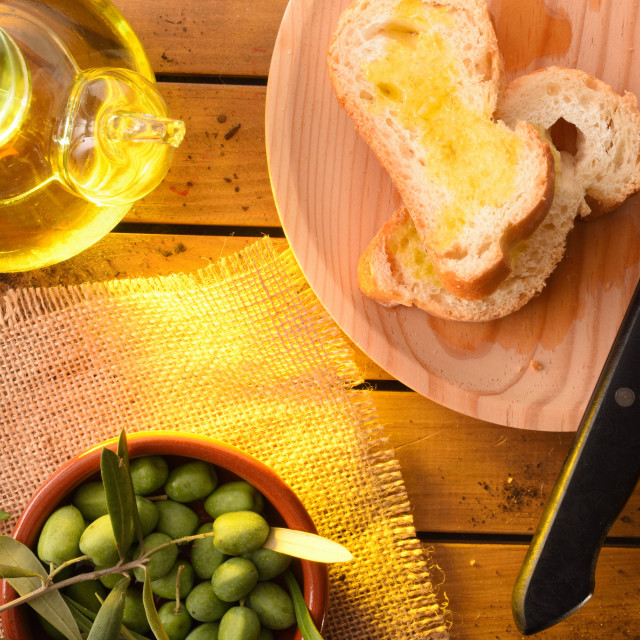 """Slices of bread with oil on wooden table countryside detail"" stock image"