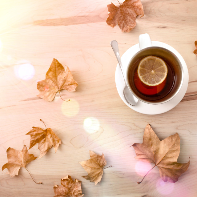 """Tea with lemon on wooden table with leaves sunny top"" stock image"