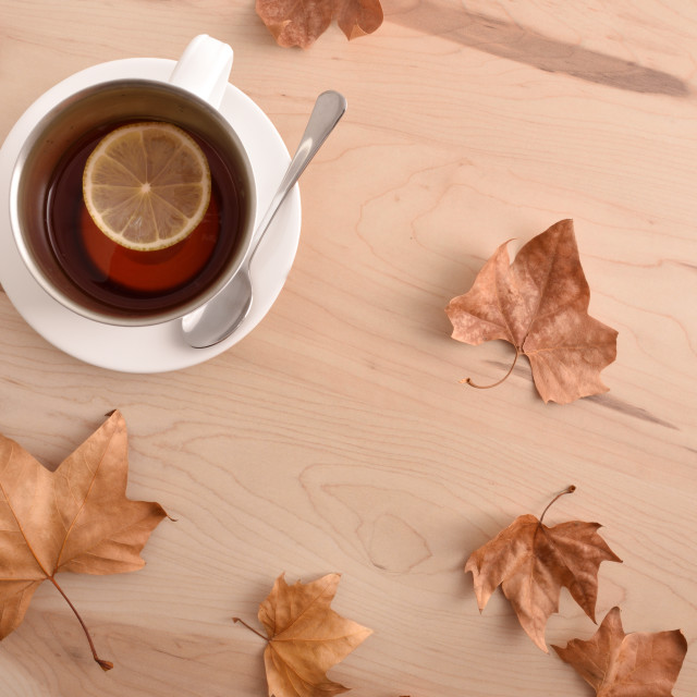 """Tea with lemon on wooden table with leaves top view"" stock image"
