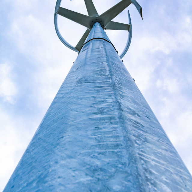 """Looking up at a small wind turbine at the top of a high metal pole"" stock image"