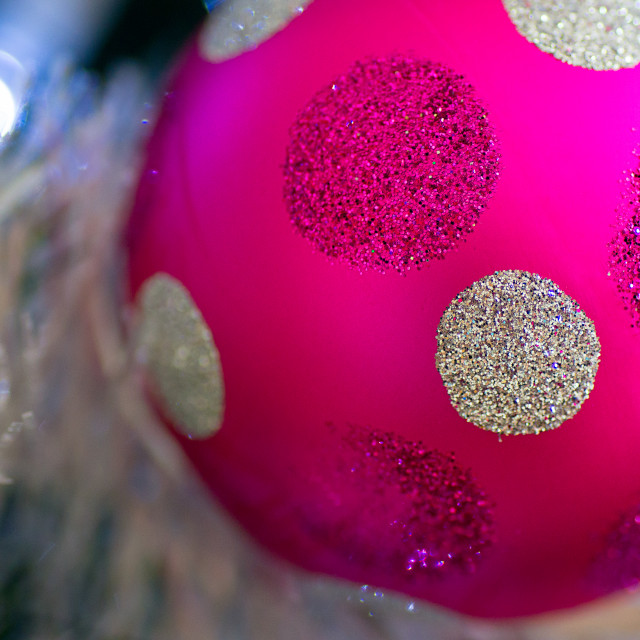 """Close-up of a pink bauble with glitter polka dots hanging in a Christmas tree"" stock image"