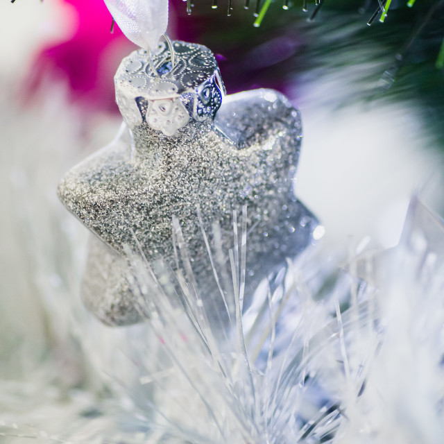 """Close up of a silver star shape ornament hanging in a Christmas tree with tinsel"" stock image"