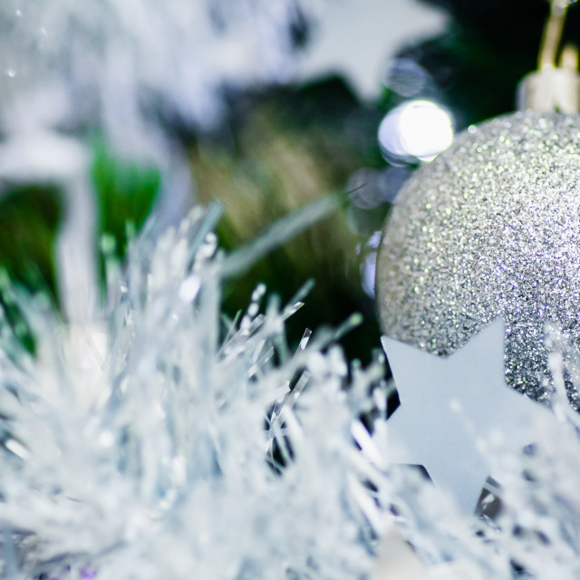 """Close-up of a silver bauble and tinsel on a Christmas tree"" stock image"