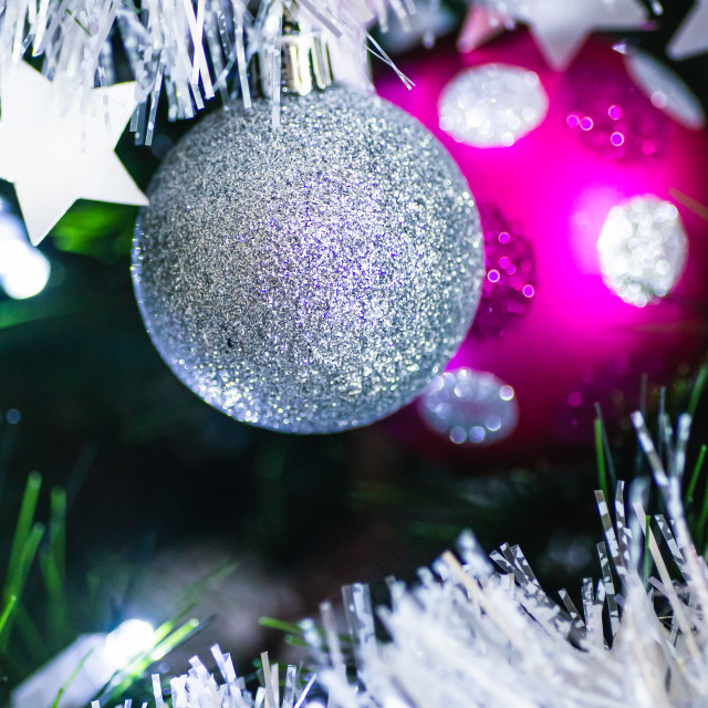 """Silver glitter bauble and a pink spotted bauble in a Christmas tree with tinsel"" stock image"
