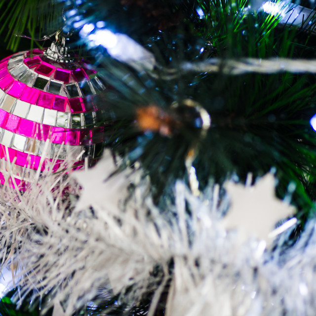 """Close-up of a pink and silver mirror ball bauble in a Christmas tree with tinsel"" stock image"