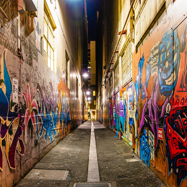 """City laneway at night with graffiti on the walls and diminishing perspective"" stock image"
