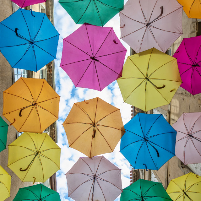 """Colorful umbrellas cover a shopping street in Carcassonne, Aude, Occitanie, France"" stock image"