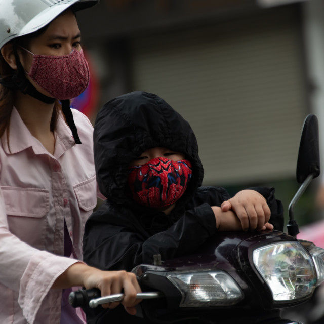 """People in Vietnam wearing facemasks against the air pollution and covid19"" stock image"