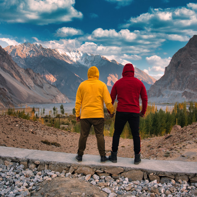 """Men with colorful dresses in front of mountains"" stock image"