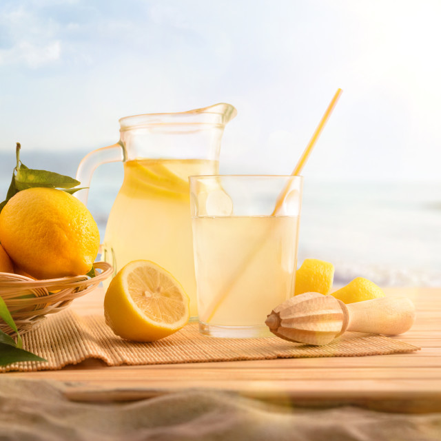 """Breakfast with Jug and glass with lemonade on the beach"" stock image"
