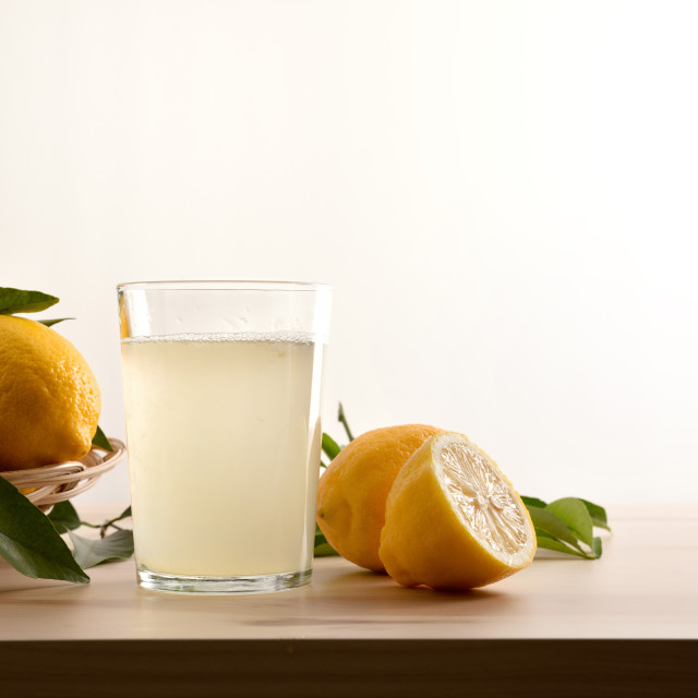 """Glass with water with lemon on wooden table white background"" stock image"