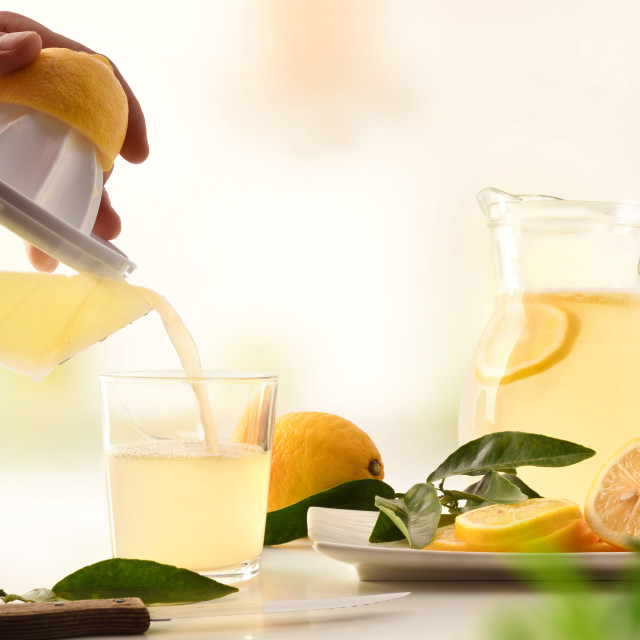 """Hands filling glass with freshly squeezed lemon juice in kitchen"" stock image"