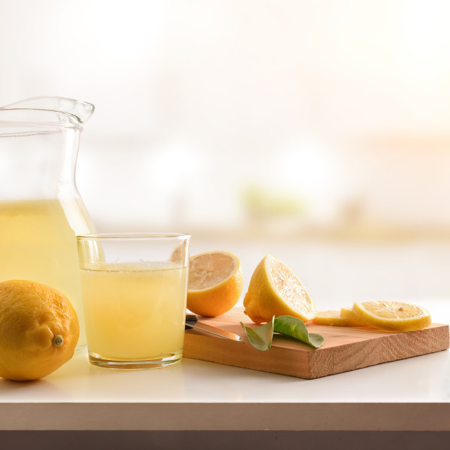 """Jug and glass filled with freshly squeezed lemon juice kitchen"" stock image"