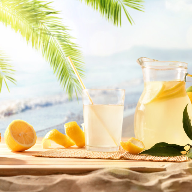 """Jug and glass with squeezed lemon juice on the beach"" stock image"
