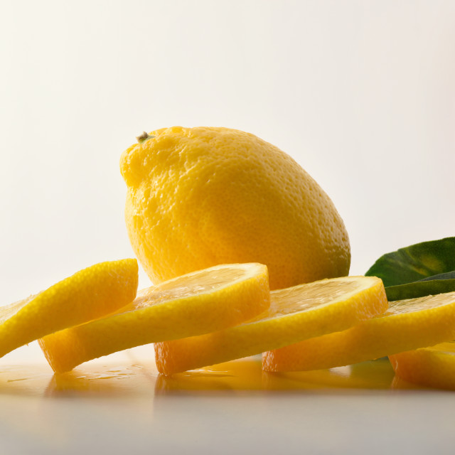 """Lemon cut into slices and leaves white isolated background"" stock image"