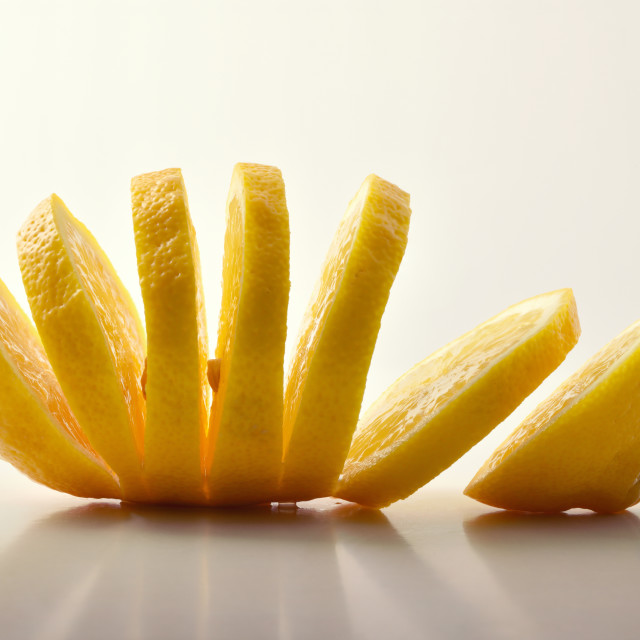 """Lemon sectioned on white table"" stock image"