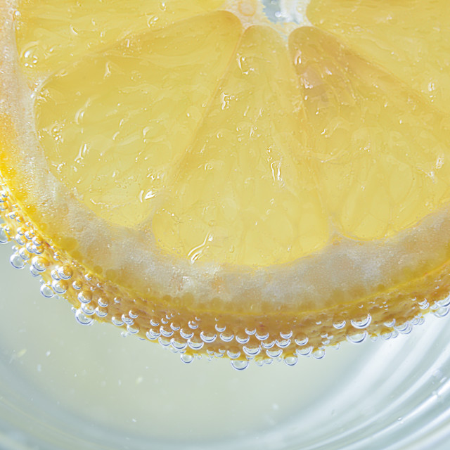 """Lemon slice floating on water in a glass"" stock image"