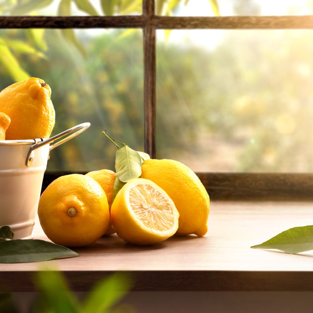 """Lemons basket on kitchen with window and orchard outside"" stock image"