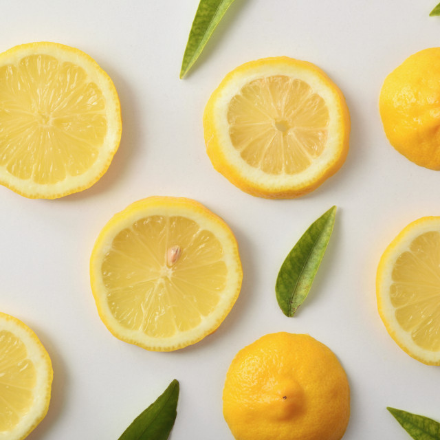 """Several lemon slices and leaves on white table top"" stock image"
