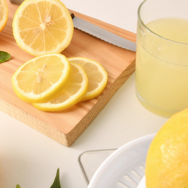 """Sliced and squeezed lemon on white table"" stock image"