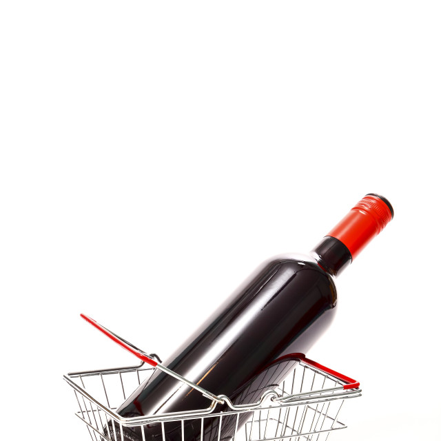 """Miniature wire shopping basket with a bottle of red wine isolated on a white background"" stock image"