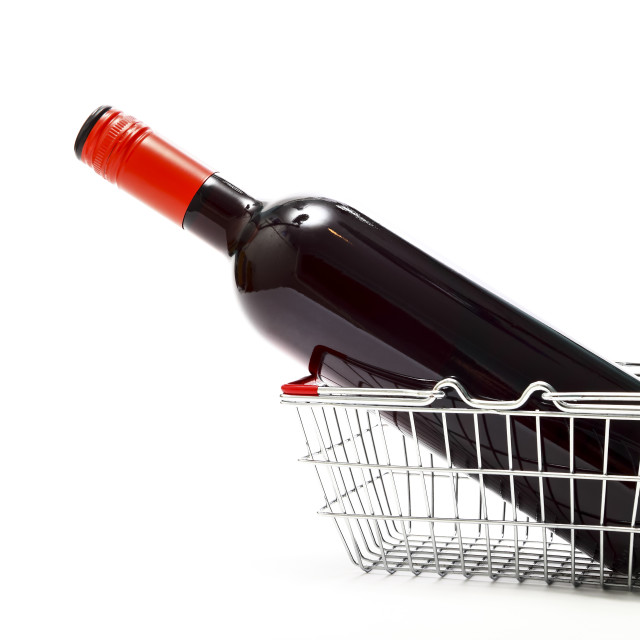"""Miniature wire shopping basket with a bottle of red wine isolated on a white background with copy space"" stock image"