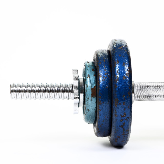 """Close up view of cast iron weights on a spinlock dumbbell bar"" stock image"