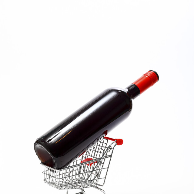 """Miniature wire shopping trolley with a bottle of red wine isolated on a white background with copy space"" stock image"