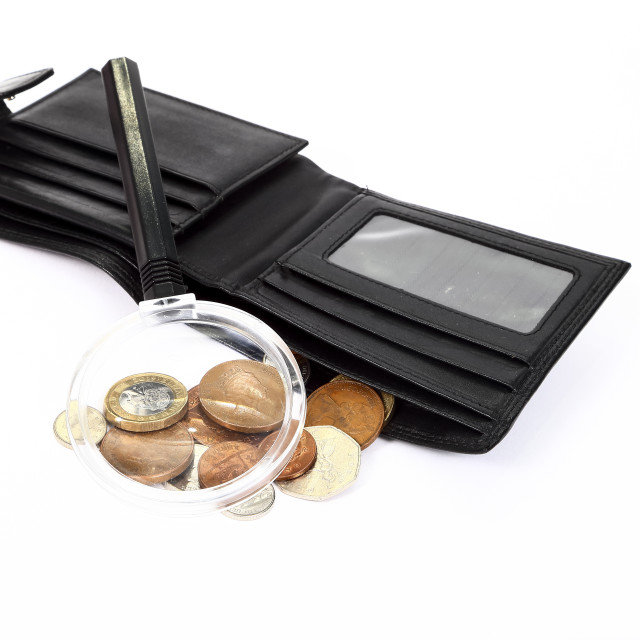 """Poverty concept with a magnifying glass and only loose change left in a leather wallet"" stock image"