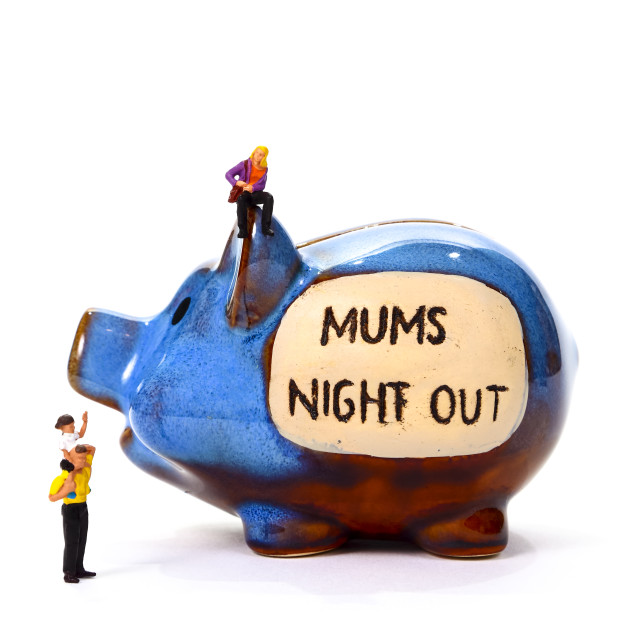"""Savings piggy bank with the words Mums Night Out and miniature figure woman man and child concept of saving up for a night out with friends"" stock image"