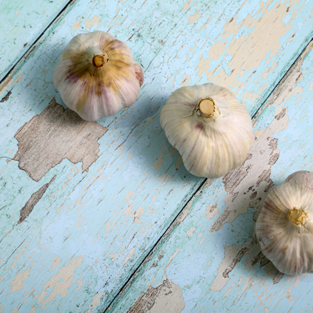 """Three garlic bulbs on a wooden textured background"" stock image"