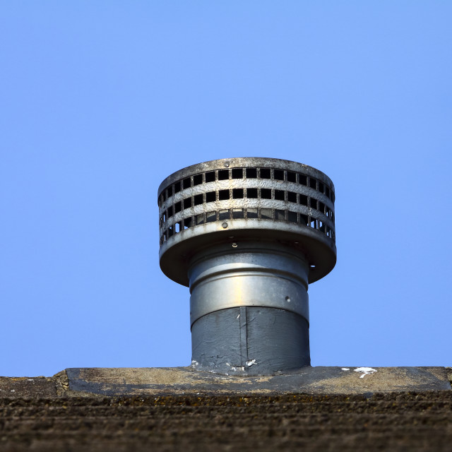 """Gas fire metal galvanized flue fitted as a replacement ridge tile to the roof of a domestic house"" stock image"