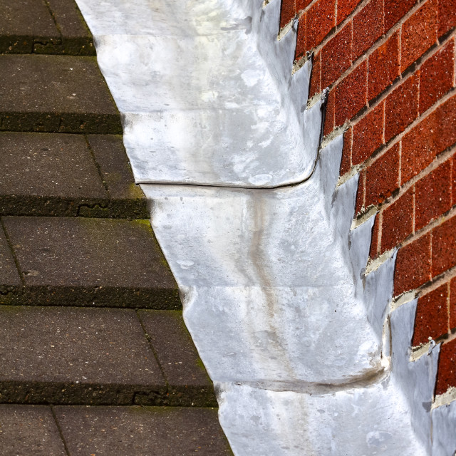 """Stepped lead flashing roof gulley creating a water tight seal between roof tiles and brick wall on a domestic house"" stock image"
