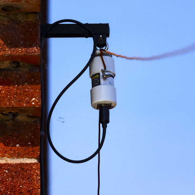 """Amateur radio long wire HF dipole antenna and balun fixed to the side of a house wall"" stock image"