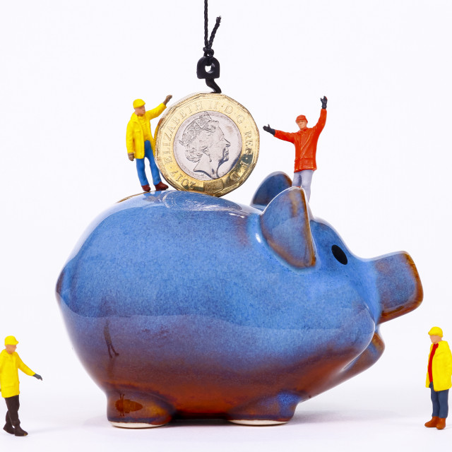 """Conceptual image of miniature figure workers lowering a pound coin in to a piggy bank"" stock image"