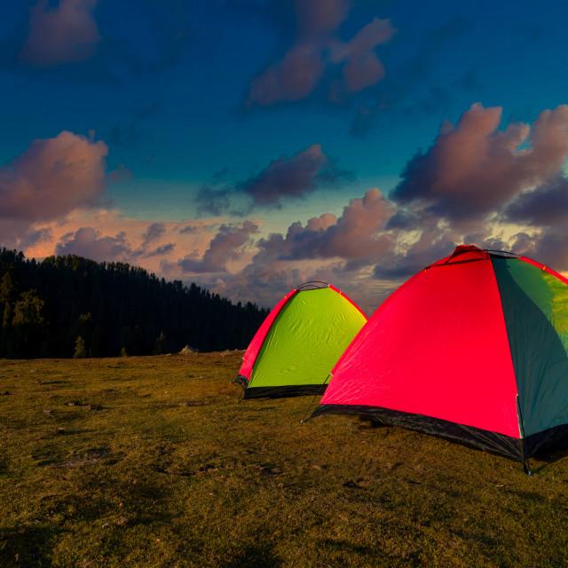 """Golden sunrise illuminating tent camping dramatic mountain landscape"" stock image"