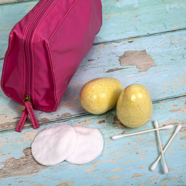 """""""Make up bag with cotton swabs pads and bath fizzers on a rustic wooden background"""" stock image"""
