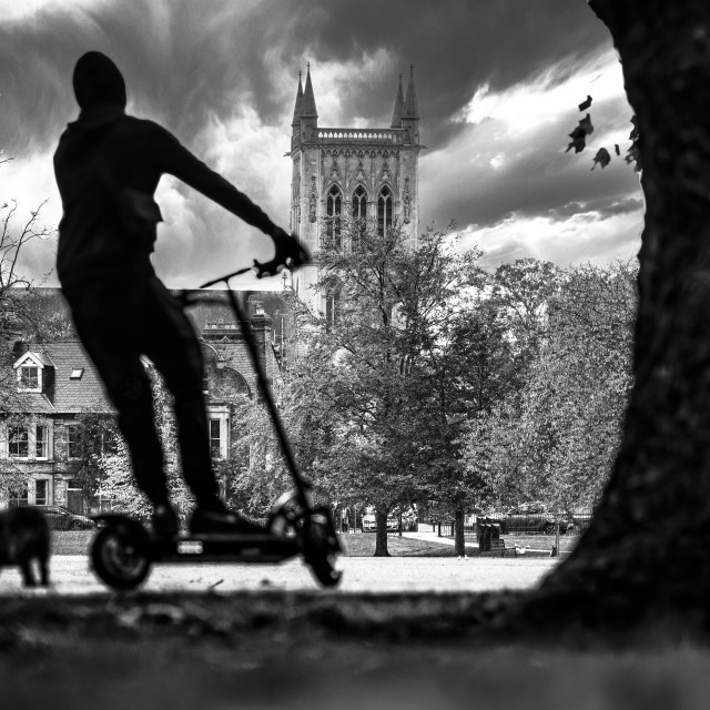 """Black and White silhouettes of a man on a scooter. Picture taken from Jesus Green, Cambridge UK."" stock image"