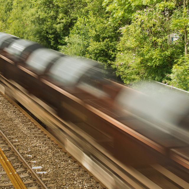 """""""Freight train at speed with slow shutter speed to show motion"""" stock image"""