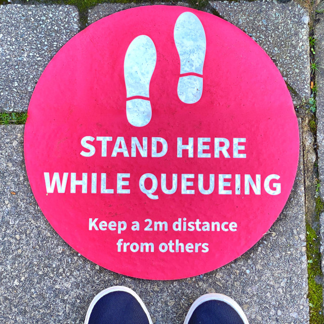"""""""Red sticker with """"Stand here"""" message for social distancing, with feet"""" stock image"""