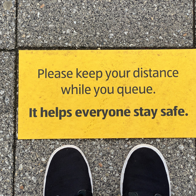 """""""Sign to encourage social distancing with feet"""" stock image"""
