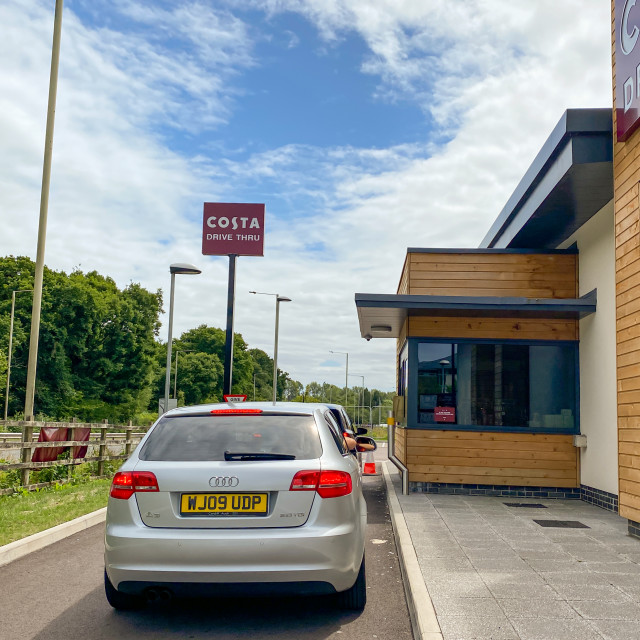 """""""Cars waiting to pick up orders from a drive thru branch of Costa Coffee"""" stock image"""