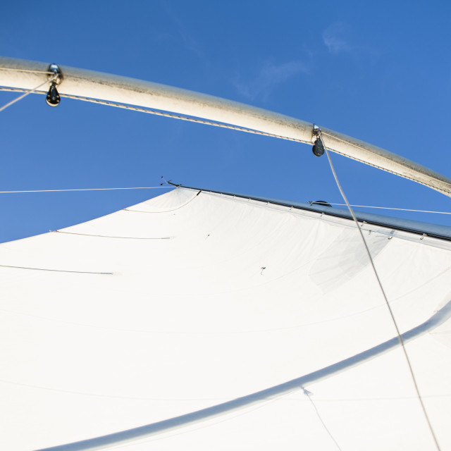 """Looking Up Minimal White Sail against Blue Sky"" stock image"