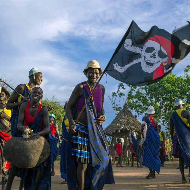 """""""Mundari tribe women with a pirate flag while celebrating a wedding, Central..."""" stock image"""