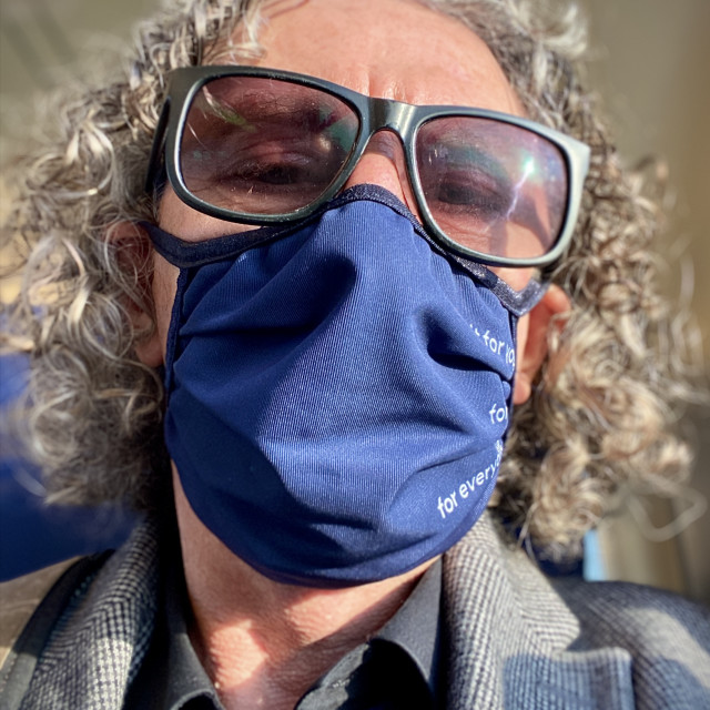 """""""Mature older caucasian man with grey curly hair wearing sunglasses and blue face mask for protection against COVID-19 corona virus spreading, traveling alone on the NS commuter train. Golden sunlight shines through carriage window. Train travel journey co"""" stock image"""