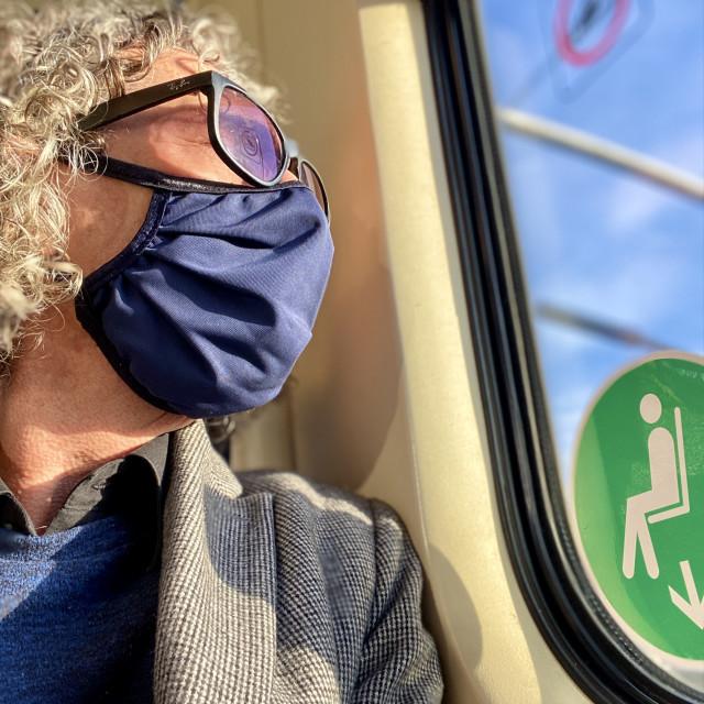 """Mature older man traveling on a commuter train during Corona epidemic wearing washable face mask."" stock image"