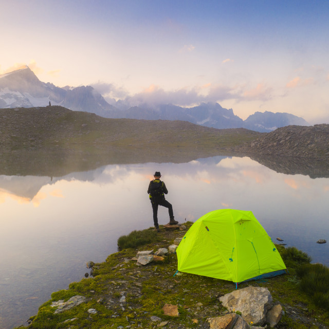 """""""Rear view of man with hat standing out of tent at Obere Schwarziseeli lake at..."""" stock image"""