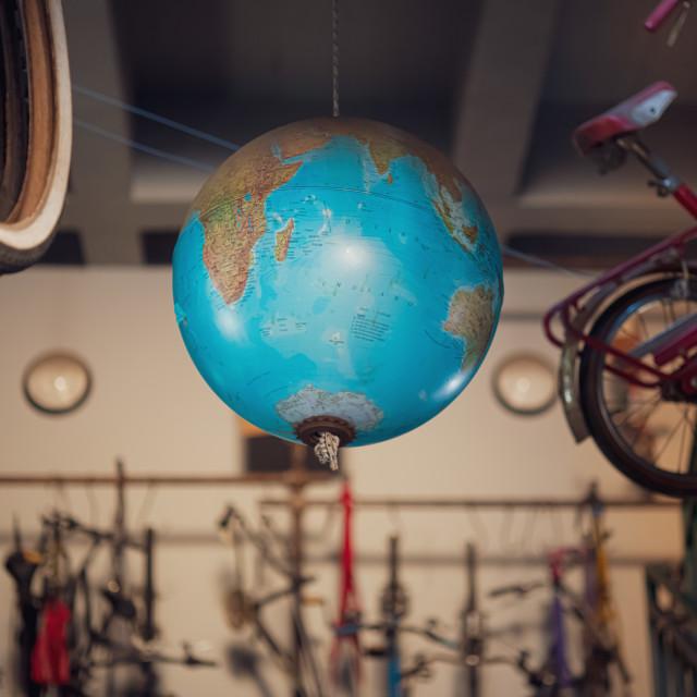 """Bicycle worldwide concept, world map globe hanging in vintage bi"" stock image"