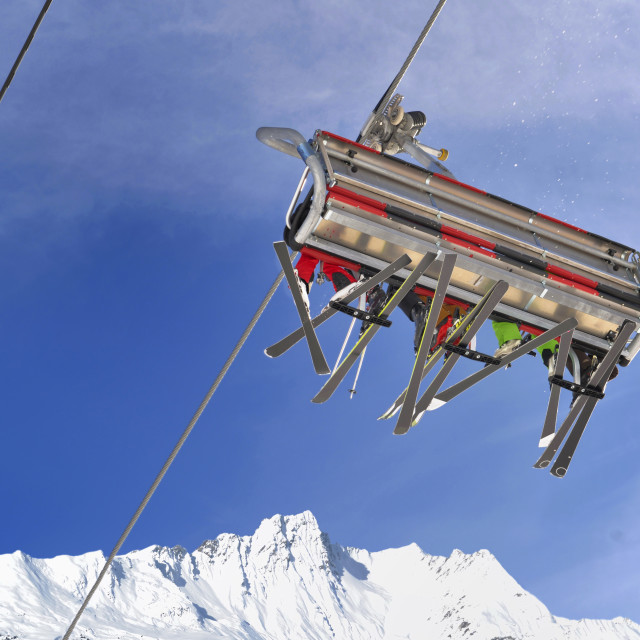 """""""view on chairlifts with skiers from below on blue sky and peak mountain snowy"""" stock image"""